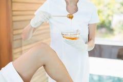 Midsection del masajista que sostiene el cuenco de la miel Imagenes de archivo