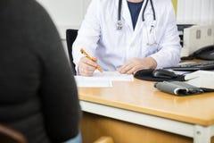 Midsection del paciente del doctor Writing Prescription For en el escritorio fotos de archivo libres de regalías