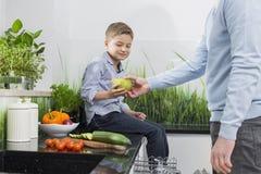 Midsection del padre que da la pera al hijo en cocina Fotos de archivo