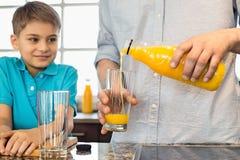 Midsection del padre que sirve el zumo de naranja para el hijo en cocina Foto de archivo libre de regalías