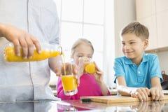 Midsection del padre que sirve el zumo de naranja para los niños en cocina Imagenes de archivo