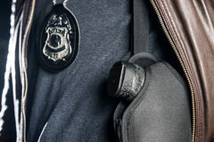 Midsection del primer del oficial de policía con la insignia y del arma en holst Imagen de archivo libre de regalías