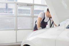 Midsection del técnico de sexo masculino que repara el motor de coche en taller imagenes de archivo