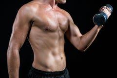 Midsection dell'atleta senza camicia che risolve con la testa di legno Fotografia Stock