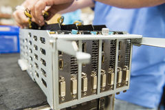Midsection dell'ingegnere maschio che ripara scheda video alla tavola nell'industria elettronica immagine stock