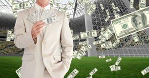 Midsection dell'uomo d'affari che mostra soldi allo stadio di football americano che rappresenta corruzione Fotografie Stock Libere da Diritti