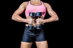 Midsection della donna che fa allenamento con le teste di legno Fotografia Stock Libera da Diritti