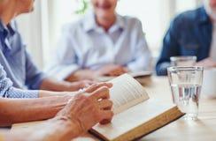 Midsection della gente senior nel gruppo della lettura della bibbia nel club del ritrovo comunale fotografia stock libera da diritti