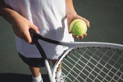Midsection della racchetta e della palla di tennis della tenuta della ragazza Fotografia Stock Libera da Diritti