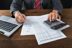 Midsection dello scrittorio di Checking Bills At dell'uomo d'affari Fotografia Stock