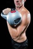 Midsection dello sportivo senza camicia che risolve con il kettlebell Fotografia Stock