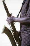 Midsection di vista laterale del primo piano dell'uomo con il sassofono Immagine Stock