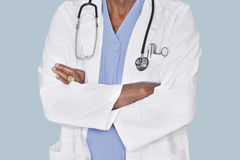 Midsection of a doctor with arms crossed over light blue background Stock Photos