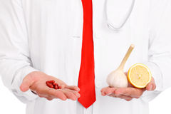 Midsection of a doctor holding pills and garlic with lemon Royalty Free Stock Photography