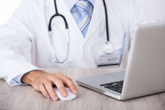Midsection of doctor using laptop and mouse at desk. Midsection of male doctor using laptop and mouse at desk in clinic stock photo