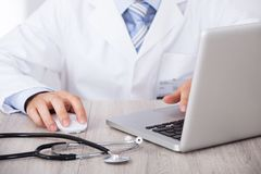 Midsection of doctor using laptop and mouse at desk. Midsection of male doctor using laptop and mouse at desk in clinic royalty free stock images