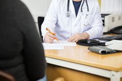 Midsection Of Doctor Writing Prescription For Patient At Desk Royalty Free Stock Photos