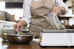 Midsection of an employee measuring ingredient on weight scale in spice store Stock Images