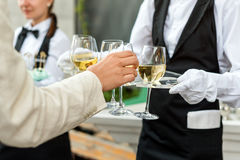 Midsection fachowy kelner w jednolitym porci winie podczas bufeta cateringu przyjęcia, świątecznego wydarzenia lub ślubu, folował fotografia stock