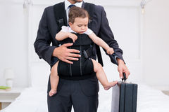 Midsection of father carrying baby while holding briefcase Stock Photo