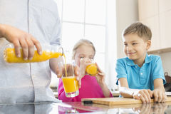 Midsection of father serving orange juice for children in kitchen Stock Images