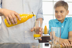 Midsection of father serving orange juice for son in kitchen Stock Images