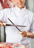 Midsection Of Female Butcher Sharpening Knife Stock Image