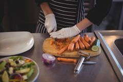 Midsection of female chef cutting carrots on board in kitchen Royalty Free Stock Image