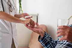 Midsection of female doctor giving medicines to senior patient. Midsection of female doctor giving medicines to patient in nursing home Stock Photo
