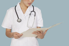 Midsection of a female doctor reading medical report over light blue background Royalty Free Stock Photo