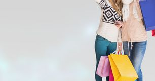Midsection of female friends with shopping bags standing against white background. Digital composite of Midsection of female friends with shopping bags standing Royalty Free Stock Photography