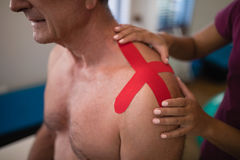 Midsection of female therapist applying elastic therapeutic tape on shoulder Royalty Free Stock Photography
