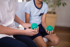 Midsection of female therapist and boy holding stress balls. At hospital ward Royalty Free Stock Photos