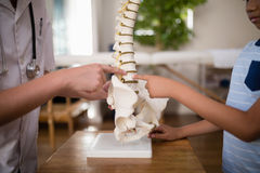 Midsection of female therapist and boy pointing at artificial spine on table. In hospital ward Stock Photography
