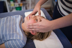 Midsection of female therapist giving head massage to boy lying on bed. At hospital ward Stock Image