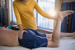 Midsection of female therapist massaging buttocks of senior male patient. At hospital ward Stock Image
