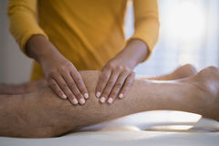 Midsection of female therapist massaging calf of male senior patient lying on bed. At hospital ward Royalty Free Stock Images