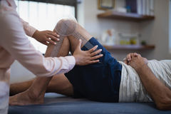 Midsection of female therapist measuring knee while senior male patient lying on bed Royalty Free Stock Photo