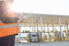 Midsection of female worker writing on clipboard while looking at truck entering in shipping yard Royalty Free Stock Photos