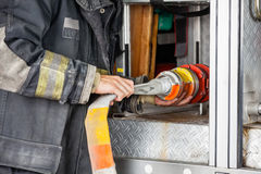 Midsection Of Firefighter Adjusting Hose In Truck Royalty Free Stock Image