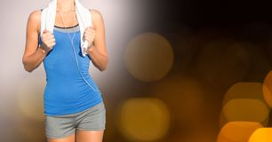 Midsection of fit woman with towel against bokeh royalty free stock photos
