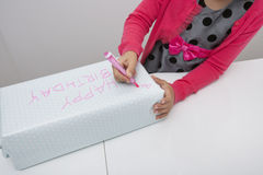 Midsection of girl writing on birthday gift at table in house Royalty Free Stock Image