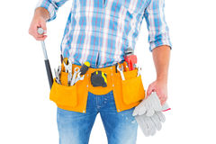 Midsection of handyman holding hammer and gloves Stock Photos