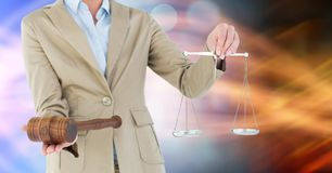 Midsection of judge holding gavel and law scales Stock Images