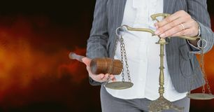 Midsection of judge holding law scales and hammer Royalty Free Stock Image