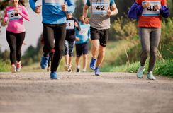 Midsection of large group of people running a race competition in nature. royalty free stock images