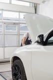 Midsection męski samochodu mechanik egzamininuje samochodowego silnika w warsztacie Fotografia Royalty Free