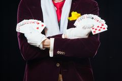 Midsection of magician showing fanned out cards against black background. Magician, Juggler man, Funny person, Black Stock Photos