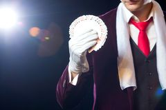 Midsection of magician showing fanned out cards against black background. Magician, Juggler man, Funny person, Black Stock Photo
