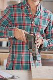 Midsection Of Male Carpenter Drilling Wood Royalty Free Stock Image